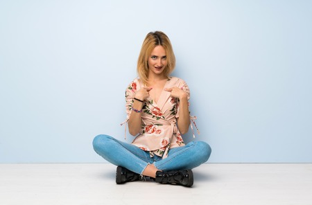 Young blonde woman sitting on the floor with surprise facial expression