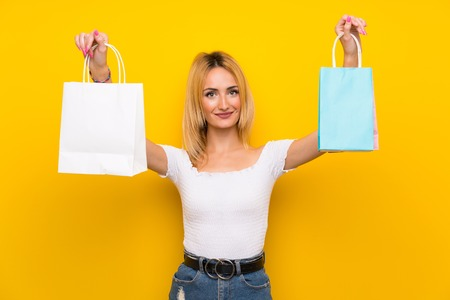 Young blonde woman over isolated yellow wall holding a lot of shopping bags