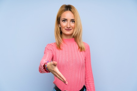 Young blonde woman with pink sweater over isolated blue background handshaking after good deal