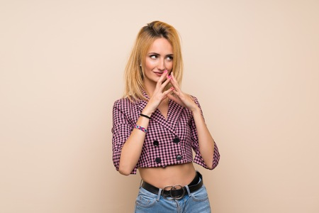 Young blonde woman with pink jacket over isolated wall scheming something Фото со стока