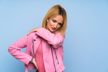 Young blonde woman with pink jacket over isolated blue background suffering from pain in shoulder for having made an effort