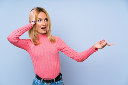 Young blonde woman with pink sweater over isolated blue background pointing finger to the side and presenting a product
