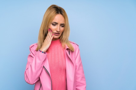 Young blonde woman with pink jacket over isolated blue background with toothache
