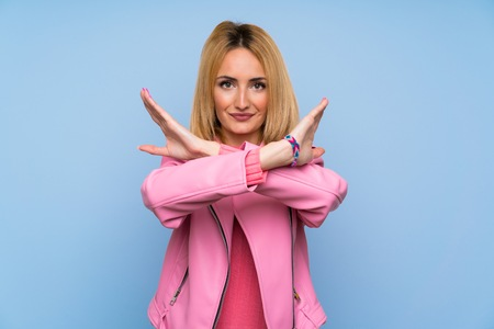 Young blonde woman with pink jacket over isolated blue background making NO gesture