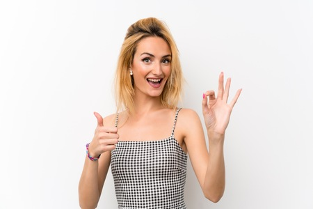 Young blonde woman over isolated white showing ok sign and thumb up gesture