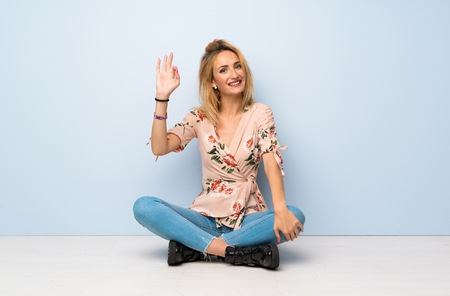 Young blonde woman sitting on the floor showing ok sign with fingers
