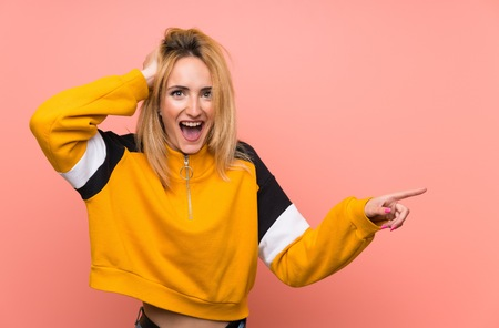 Young blonde woman over isolated pink background surprised and pointing finger to the side