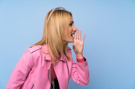 Junge blonde Frau mit rosa Jacke über isoliertem blauem Hintergrund schreien mit weit geöffnetem Mund zur Seite Standard-Bild