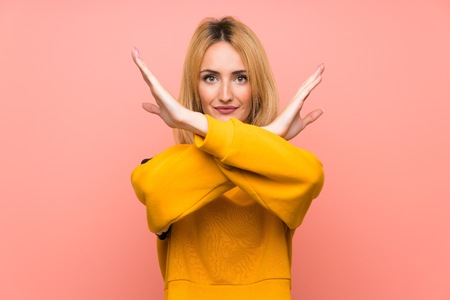 Young blonde woman over isolated pink background making NO gesture