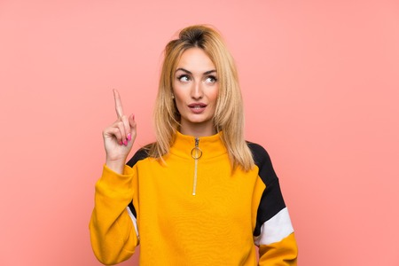 Young blonde woman over isolated pink background thinking an idea pointing the finger up
