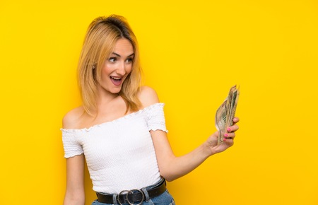 Young blonde woman over isolated yellow wall taking a lot of money