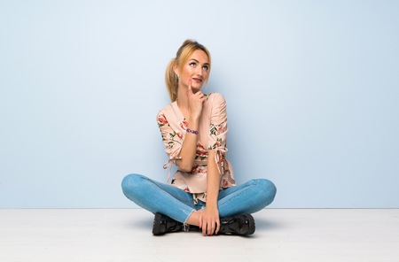 Young blonde woman sitting on the floor thinking an idea while looking up