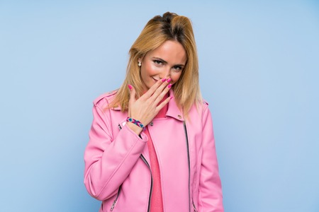 Young blonde woman with pink jacket over isolated blue background smiling a lot