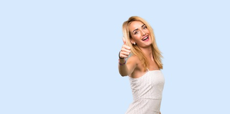 Young blonde woman with thumbs up because something good has happened over isolated blue background