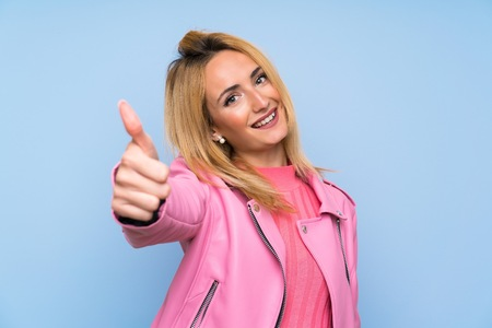 Young blonde woman with pink jacket over isolated blue background with thumbs up because something good has happened