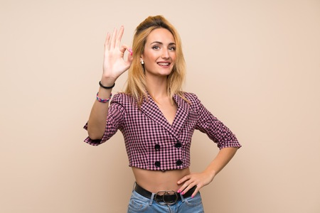 Young blonde woman with pink jacket over isolated wall showing ok sign with fingers