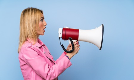Young blonde woman with pink jacket over isolated blue background shouting through a megaphone Foto de archivo - 124804055