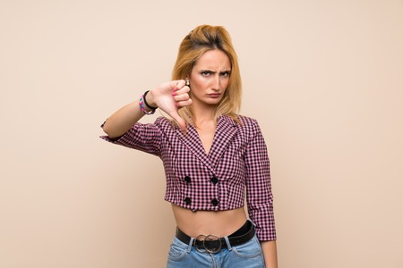 Young blonde woman with pink jacket over isolated wall showing thumb down with negative expression Reklamní fotografie