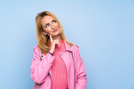 Young blonde woman with pink jacket over isolated blue background thinking an idea while looking up