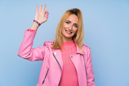 Young blonde woman with pink jacket over isolated blue background showing ok sign with fingers 스톡 콘텐츠