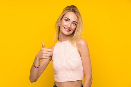 Young blonde woman over isolated yellow wall giving a thumbs up gesture