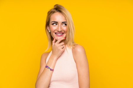 Young blonde woman over isolated yellow wall thinking an idea