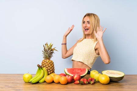 Young blonde woman with lots of fruits with surprise facial expression
