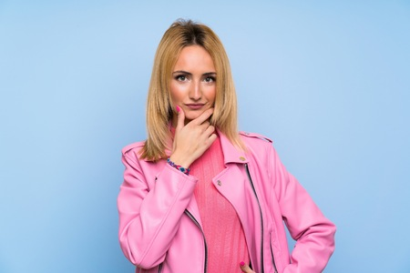Young blonde woman with pink jacket over isolated blue background thinking