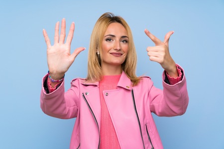 Young blonde woman with pink jacket over isolated blue background counting seven with fingers