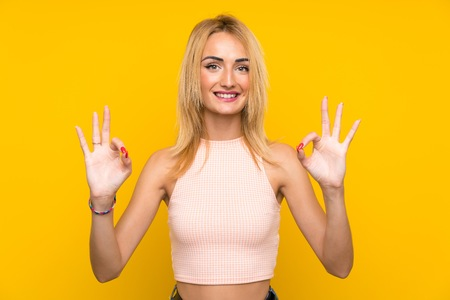 Young blonde woman over isolated yellow wall showing an ok sign with fingers