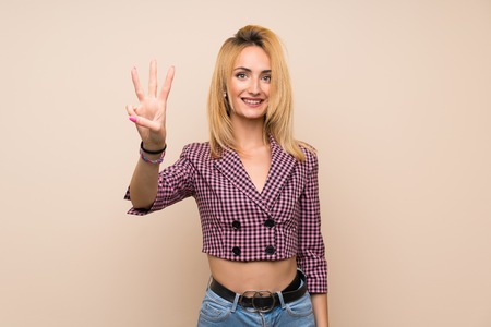 Young blonde woman with pink jacket over isolated wall happy and counting three with fingers