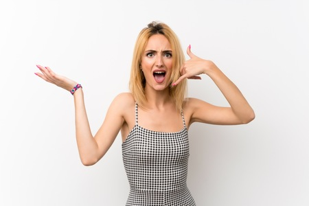Young blonde woman over isolated white making phone gesture and doubting 스톡 콘텐츠