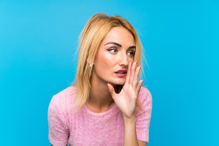 Young blonde woman over blue background whispering something