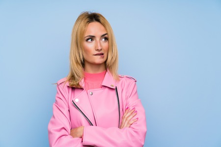 Young blonde woman with pink jacket over isolated blue background with confuse face expression