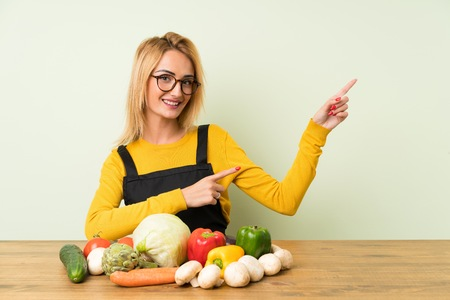 Young blonde woman with lots of vegetables pointing finger to the side