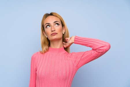 Young blonde woman with pink sweater over isolated blue background standing and thinking an idea