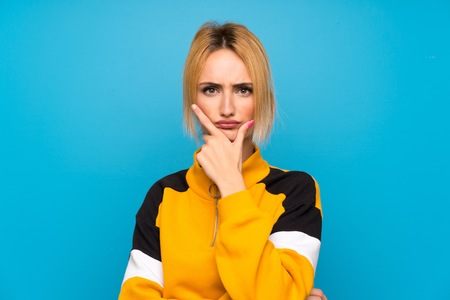 Young blonde woman over isolated blue background standing and thinking an idea