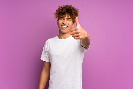 Young african american man over isolated purple wall with thumbs up because something good has happened