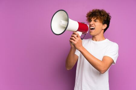 Young african american man over isolated purple wall shouting through a megaphone