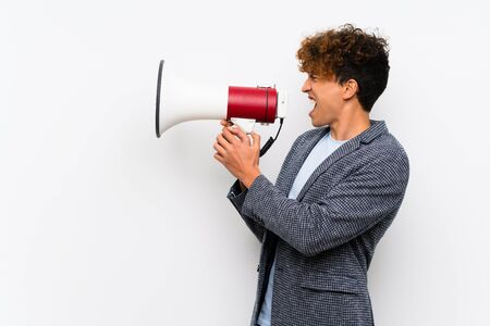 Fashion african american man over isolated white wall shouting through a megaphone Stock Photo