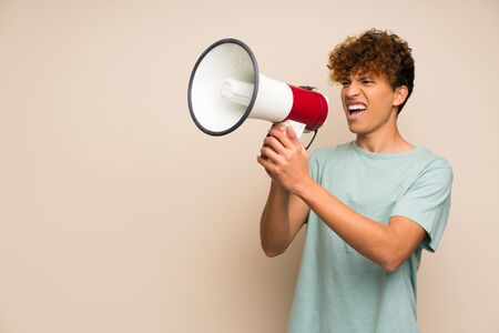 African american man with green shirt shouting through a megaphone Stock Photo