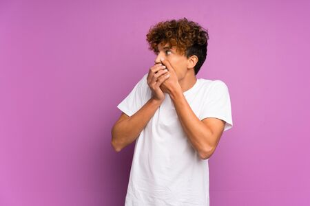 Young african american man over isolated purple wall covering mouth and looking to the side