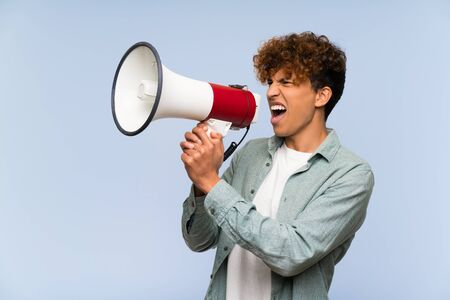 Young african american man over isolated blue wall shouting through a megaphone Stock Photo