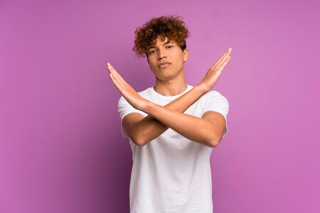 Young african american man over isolated purple wall making NO gesture