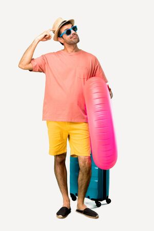 Full body of Man with hat and sunglasses on his summer vacation having doubts and with confuse face expression while scratching head on isolated background Stock Photo - 124924871
