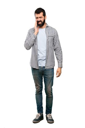 Handsome man with beard with toothache over isolated white background