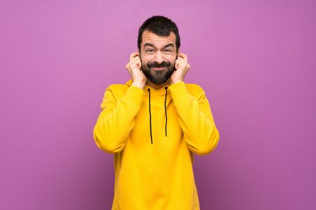 Handsome man with yellow sweatshirt frustrated and covering ears