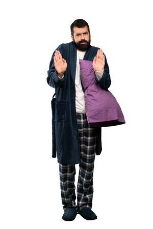 Man with beard in pajamas making stop gesture and disappointed over isolated white background