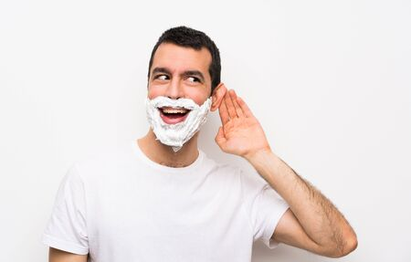 Man shaving his beard over isolated white background listening to something by putting hand on the ear