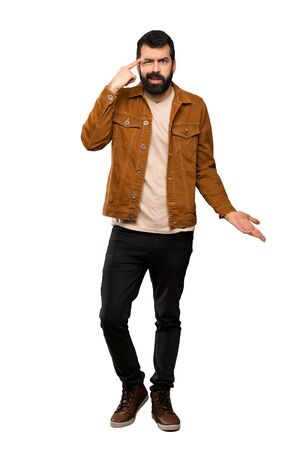 Handsome man with beard making the gesture of madness putting finger on the head over isolated white background